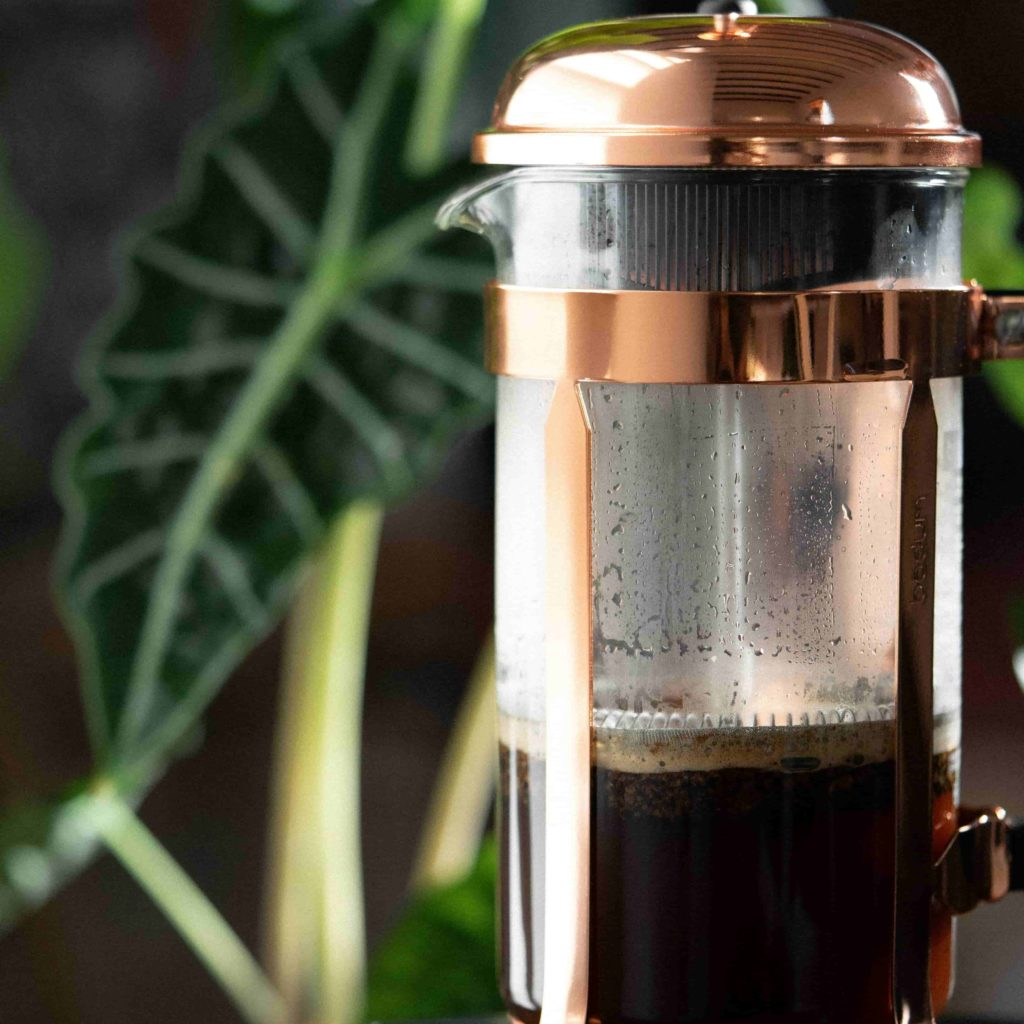 Classic Bodum  Glass French Press in Copper on top of a black Acaia digital scale with indoor plants background