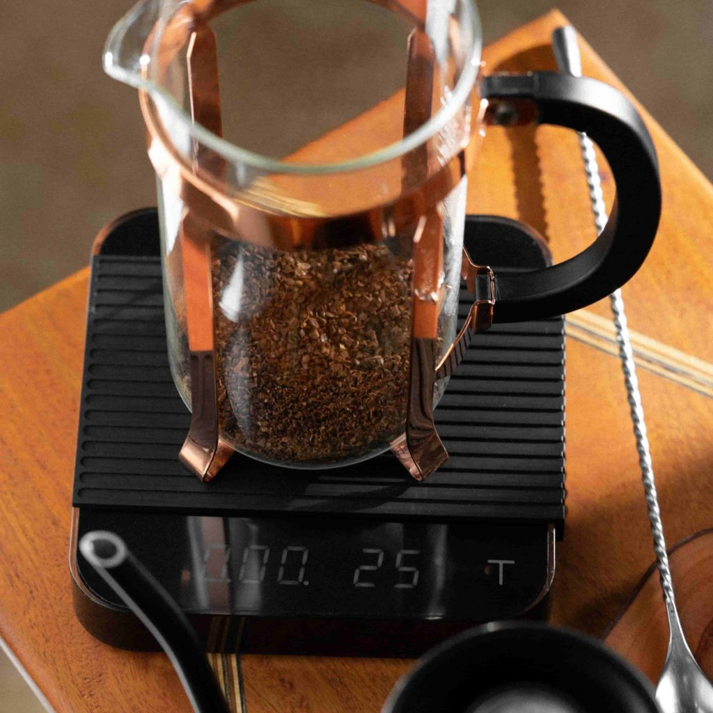 Classic Bodum Glass and Copper French press on top of a black Acaia coffee scale next to a Fellow kettle and bar spoon on a wooden table surface