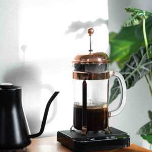 A matte black Fellow Kettle next to a freshly roasted brewed coffee from Puerto Rico in a Copper Bodum French Press on top of a Acaia Coffee Scale