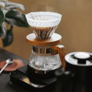 Brewing at home Glass Hario V60 with Olive Wood Trim Coffee Decanter on top of Acaia coffee scale next to a hot kettle