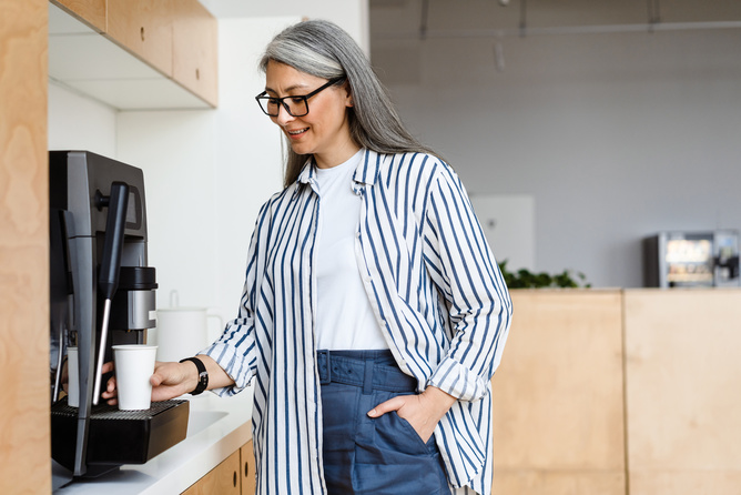 Happy white-haired mature woman smiling while using coffee maker at the office